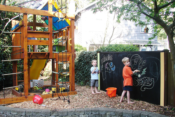 Outdoor space with kid-friendly playhouse and DIY chalkboard