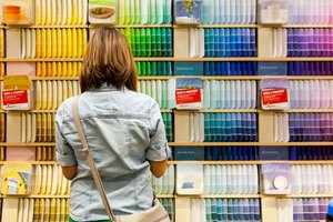 Woman standing in front of a wall of paint colors