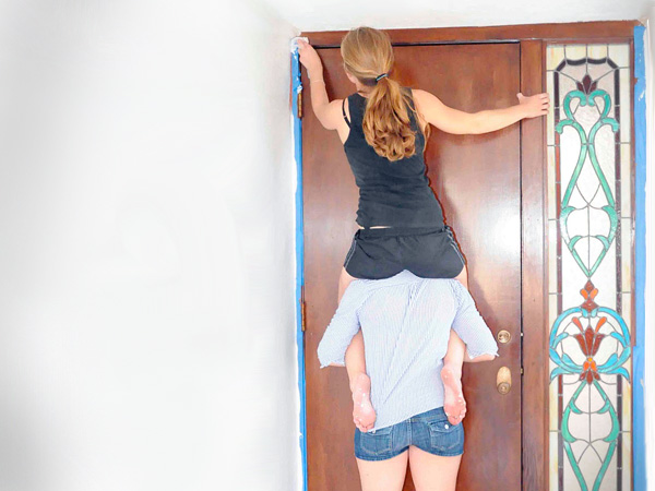 Human stepladder to clean the top of a doorframe