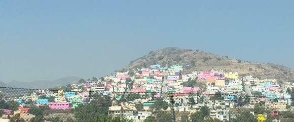 Colorful houses on the side of a hill on the way to the pyramids