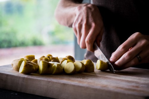 slicing fingerling potatoes into bite-sized pieces