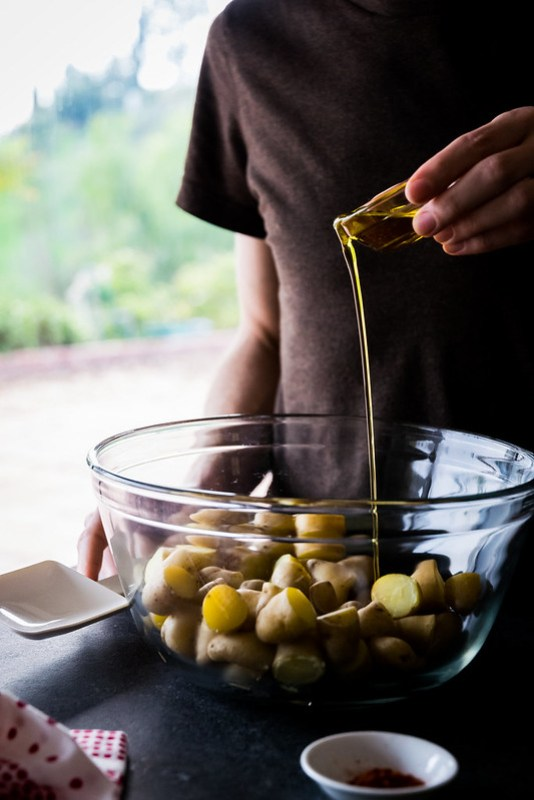 tossing the cooked potatoes with olive oil and spices