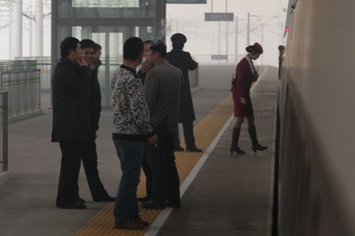 Smokers have a quick puff during the station stop at Handan East