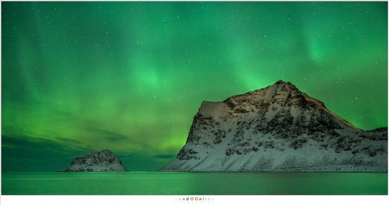 Een hemel vol Aurora Borealis boven het strand van Vik