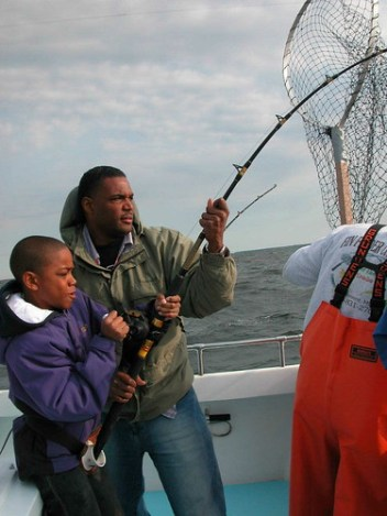 Photo of man and son reeling in a big one