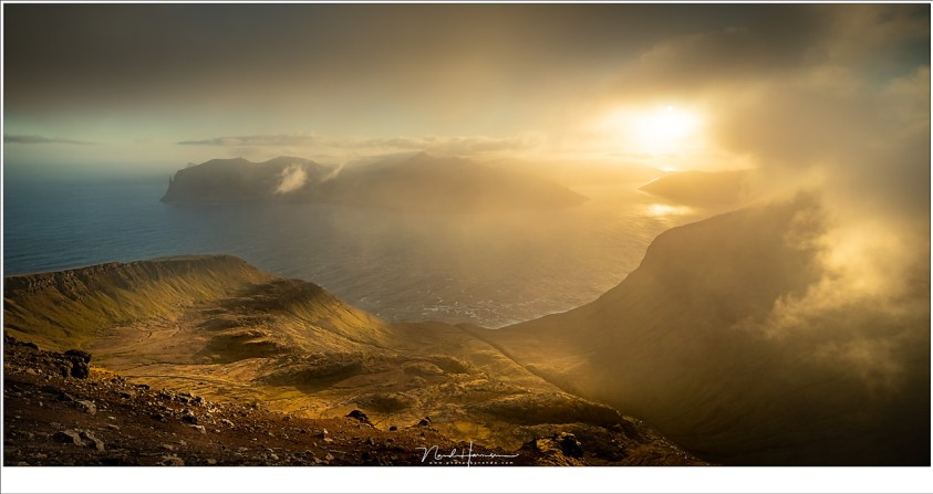 Uitzicht over het eiland Vàgar met een glimp van de rots Trøllkonufingur links in de verte. het ene moment bevonden we ons in de mist, het volgende moment opende het uitzicht in volle glorie (18mm | ISO200 | f/11 | 1/400)