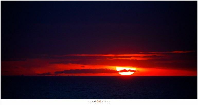 Vlak voor de zon de horizon raakt, omlijst door de wolken en de wereld (EOS 5D mark IV + EF100-400L II @ 400mm | ISO800 | f/5,6 | t=1/2500sec)