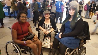 3 wheelchair users, oneyoung black, one middle aged East Asian and another white young woman. They are smiling at the camera.e