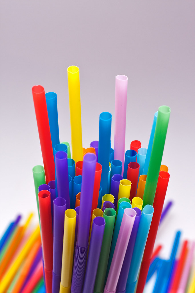 A Bunch Of Colorful Plastic Straws In A Glass Lots Of