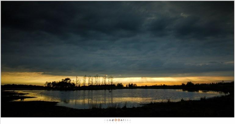 Het einde van de dag, als de zon de horizon nadert. Wolken heersen nog over de hemel, maar zullen spoedig vluchten