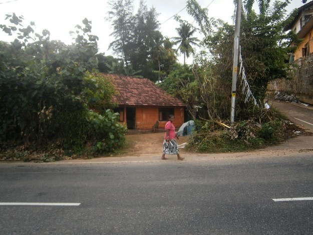 Woman walking in front of her house