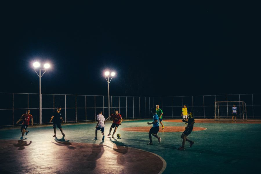 Men playing street football at night.