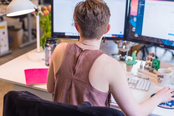 person working at desk for full-time job miss millennia magazine