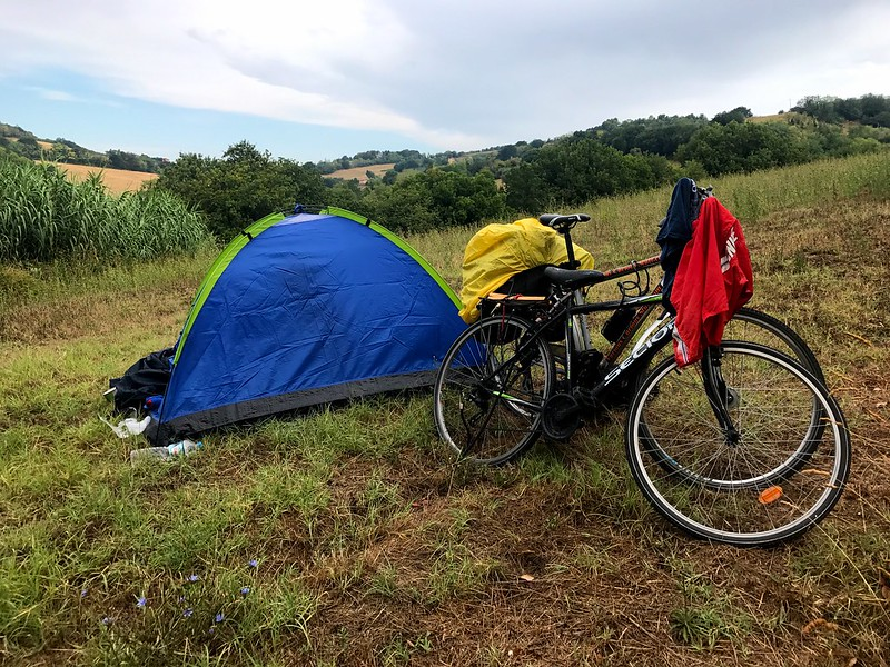 camping in a field while on a cycling trip in italy