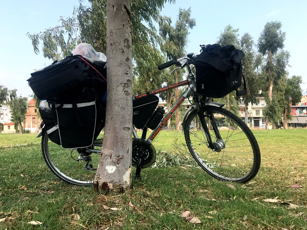 loaded touring bike propped against eucalyptus tree in patras, greece
