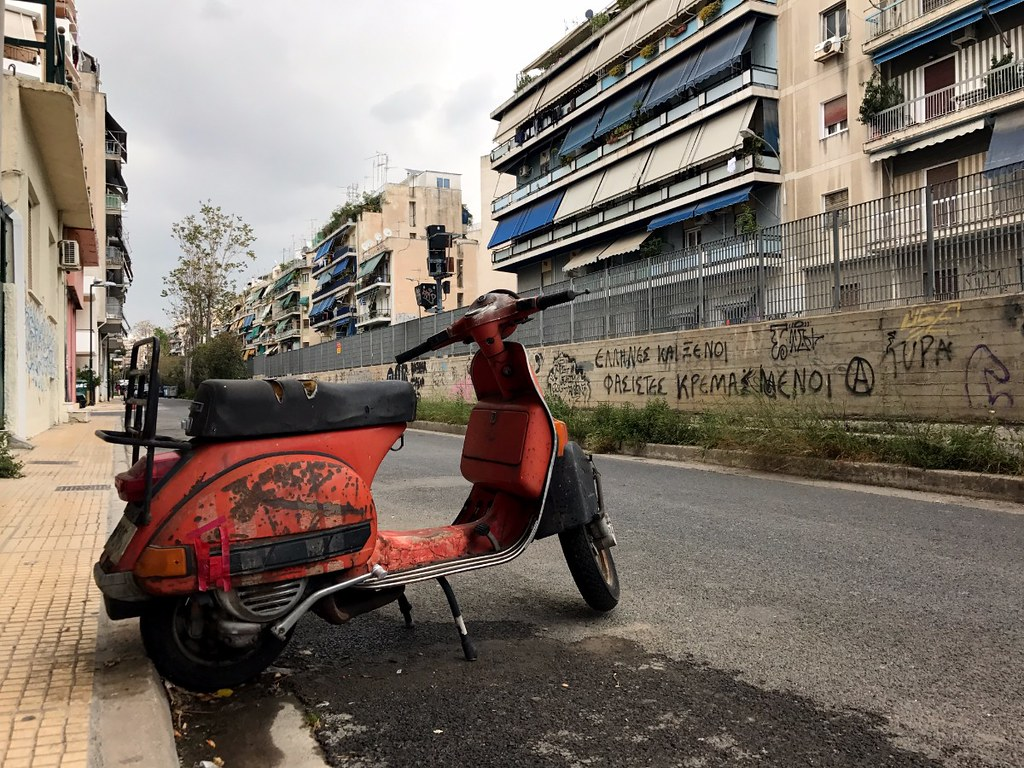 old red vespa in a dirty street in kato patisia athens
