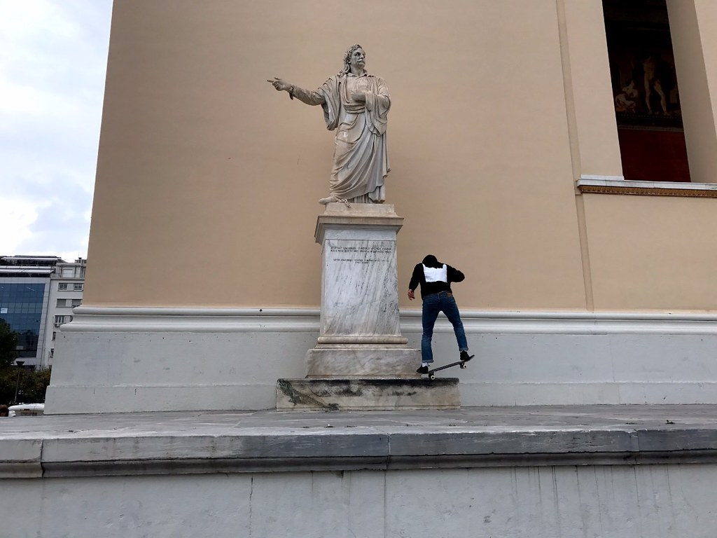 skater grinding on a statue base in front of athens university