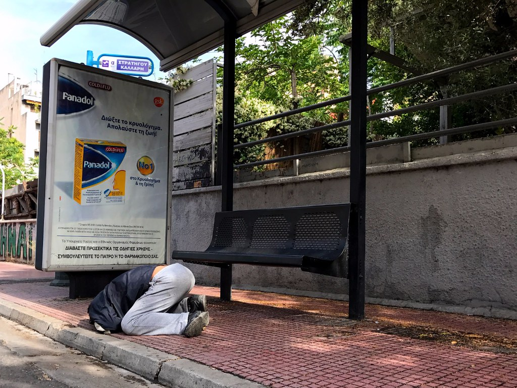 beggar sleeping on his knees face down in front of bus stop in athens
