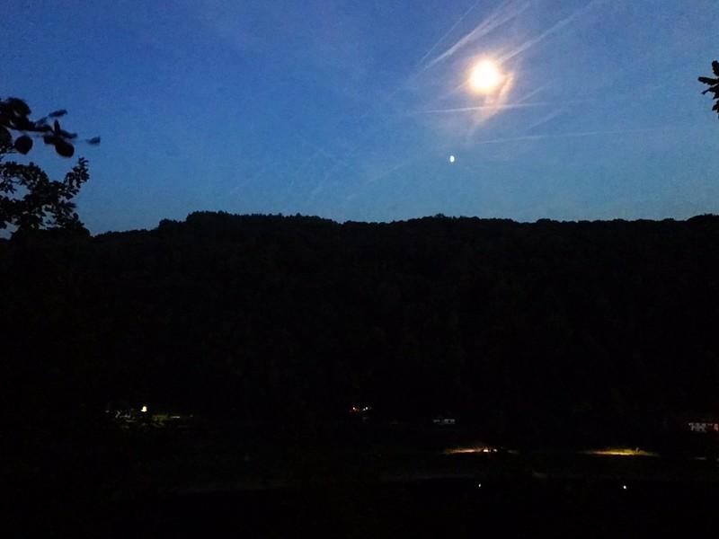 full moon rising over dark hills in saxon switzerland