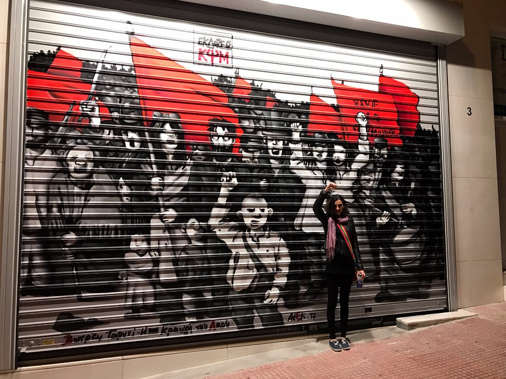 graffiti of black human figures raising red flags in the streets of exarcheia in athens