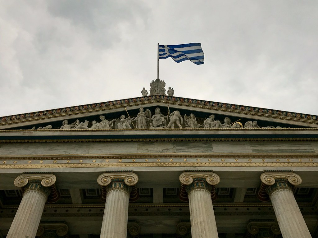 pediment of athens university building with the greek flag waving over it