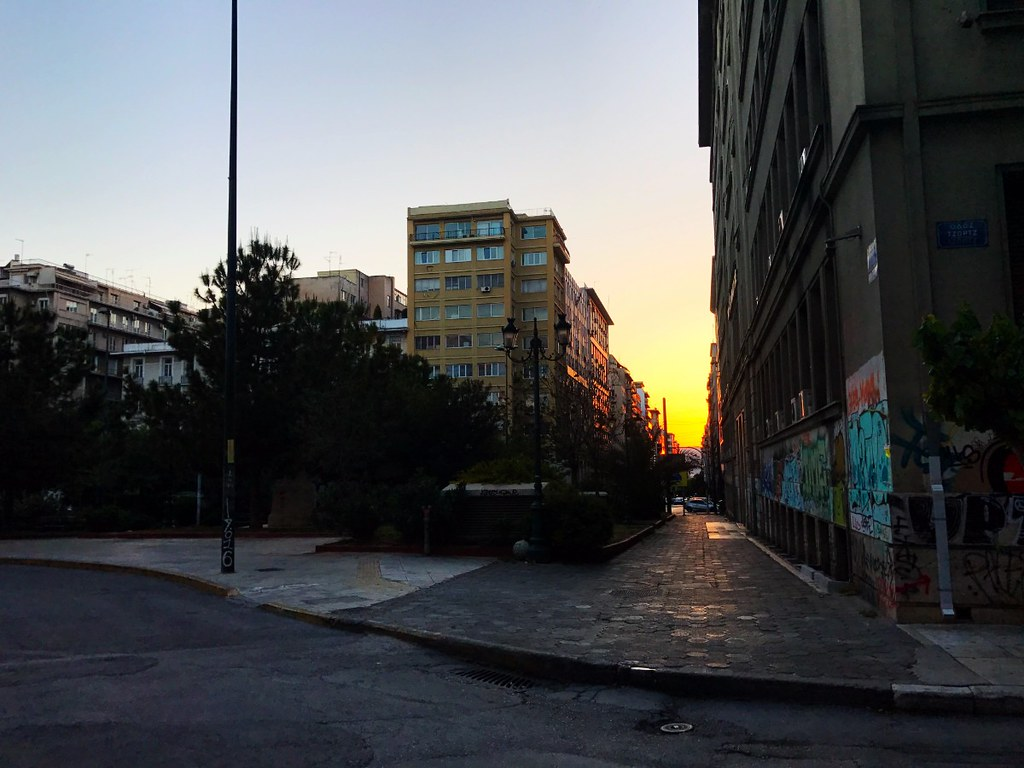 sun setting in the depth of long street looking west in athens