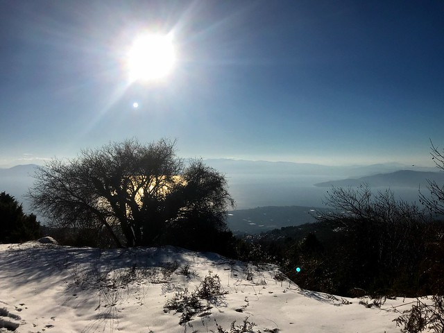 bright sun, snow-clad mountains, and blue sea in mount pelion in greece