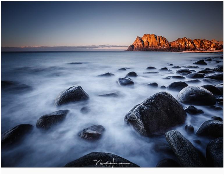Het strand van Uttakleiv als het laatste licht van de dag de verre berg nog even in het zonnetje zet