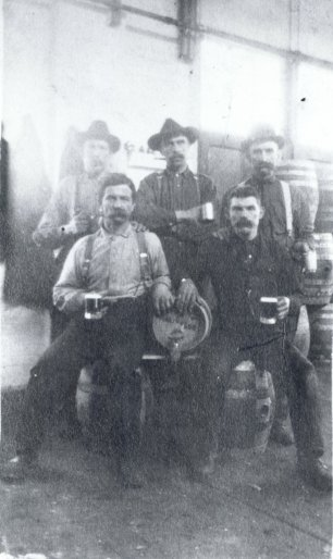 Men sitting with kegs, holding glasses of beer