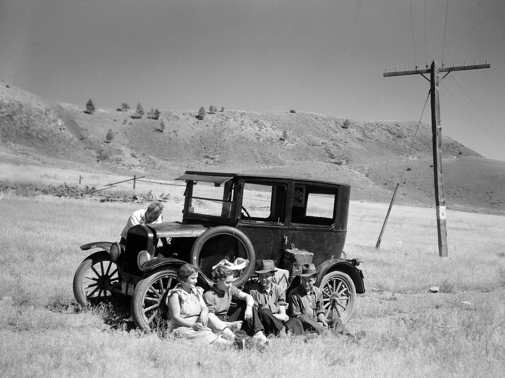 Rothstein, Arthur, photographer. Vernon Evans and family of Lemmon, South Dakota, near Missoula, Montana, Highway 10. Leaving the grasshopper-ridden and drought-stricken area for a new start in Oregon and Washington. Expect to arrive at Yakima in time for hop picking. Make about two hundred miles a day in Model T Ford. Live in tent. July, 1936.