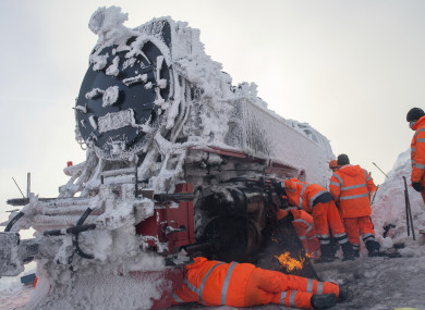 Workers de-ice parts on a classic steam locomotive in Germany.