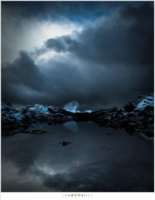 De donkere wolken van de sneeuwstorm zetten hun weg naar de eilanden voort. als de bewolking breekt is het magisch. Een poel water tussen de rotsen verraad geen wilde zee achter de rotsen. Maar de branding is wild genoeg om het water hoog boven de barrière op te jagen.