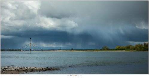 Regenbuien boven de Waal bij Tiel. Grillige wolken en striemen van regen maken de lucht erg interessant
