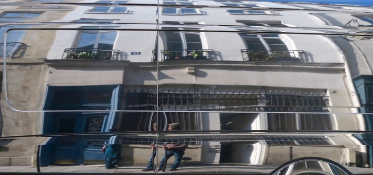 the reflection of our front building in the shiny black van opposite