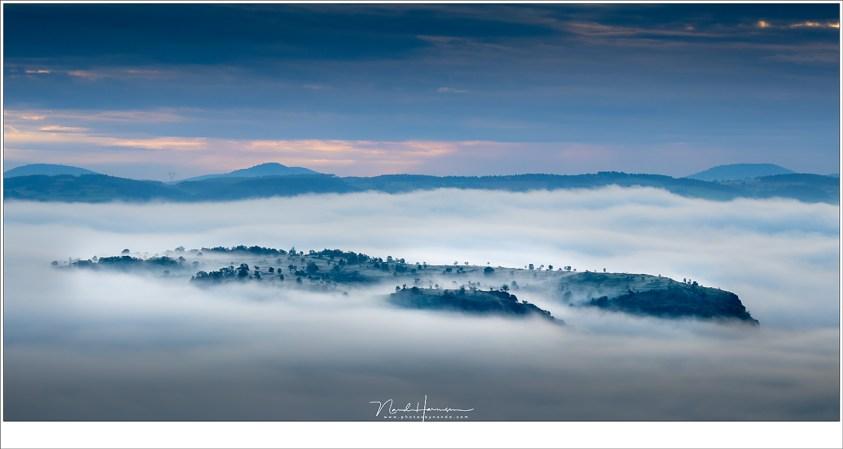 Niet alleen de burcht van Polignac steekt boven de wolken uit, her en der breekt de top van een heuvel door de mist, als eilanden waar vingers van mist overheen kruipen. (EOS M50 + EF-M18-150mm @ 66mm   ISO125   f/8   1/125)