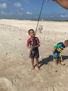 Photo of Boy with his catch of a pompano on the beach