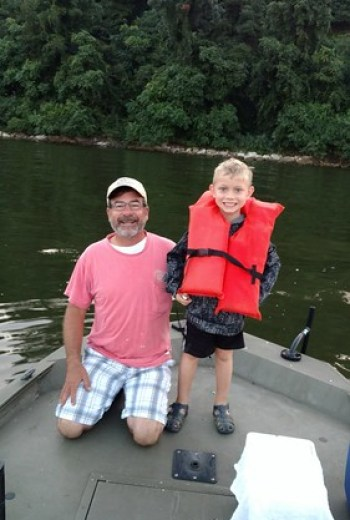 Boy and his grandfather on a boat.