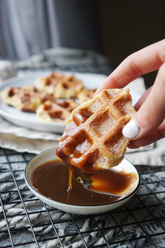 Gluten free waffle churros covered in cinnamon sugar and dipped in a homemade caramel sauce