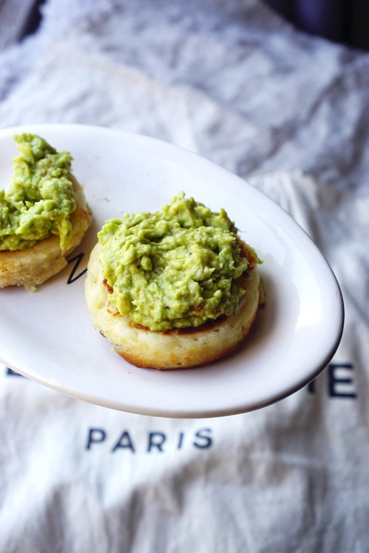 Homemade gluten free crumpets with mashed avocado.