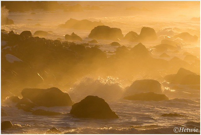 Gouden zonnestralen verlichten het water en de rotsen