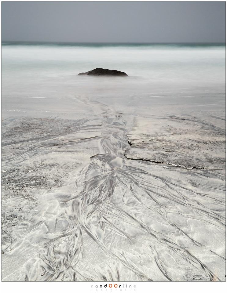 Patronen in het zand, de weg van het terugkerende water. Details van het water zijn verdwenen door de lange sluitertijd om aandacht op de patronen te vesttigen