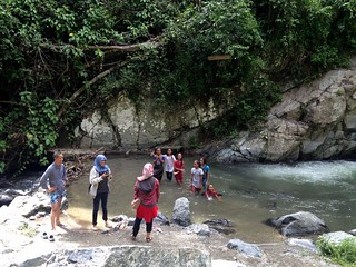 indonesian family spending weekend in wera waterfalls in palu, sulawesi