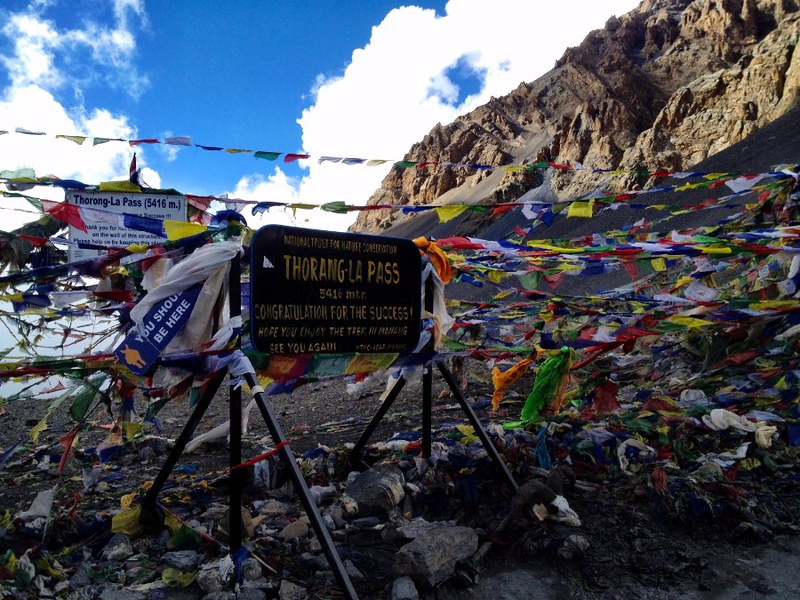 flags and sign at thorung la pass in annapurna