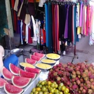 Pedagang buah dan baju yang berdampingan