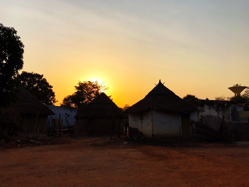 sunrise over traditional african huts in niokolo koba national park