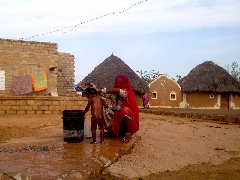 indian woman washing a boy in desert village in rajasthan