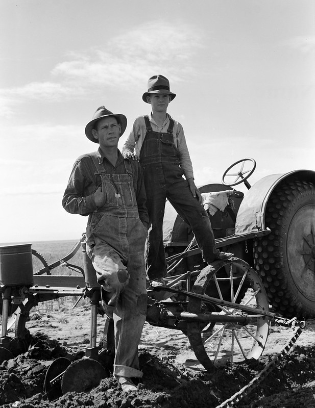 Dust bowl farmer with tractor and young son near Cland, New Mexico. Dust bowl farmer with tractor and young son near Cland, New Mexico. June 1938.