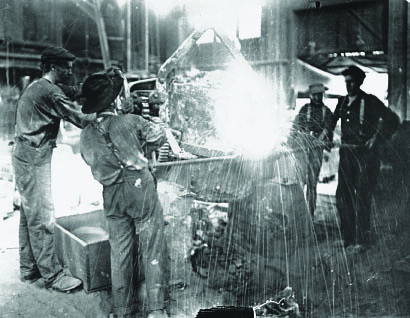 Interior View Of A Steel Mill Featuring Workers Title
