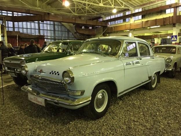 на переднем плане автомобиль такси ГАЗ 21 Волга третьей серии (1962-1970), на дальнем плане ГАЗ 24-95
