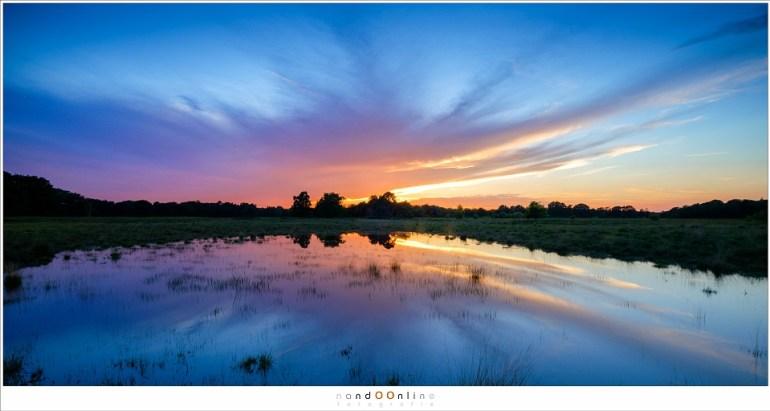 Een typisch landschap: prachtige wolken met wonderlijke kleuren, gereflecteerd in een ven op de Strabrechtse Heide